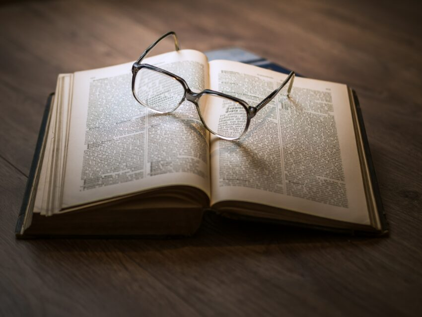 framed eyeglasses on top open book
